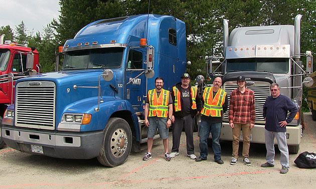 Picture of group of people standing in front of semi-trucks.