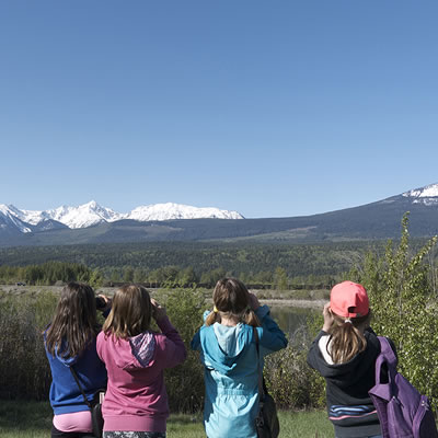 A picture of a group of kids, backs turned towards the viewer, looking at a scenic expanse of mountains in the distance.