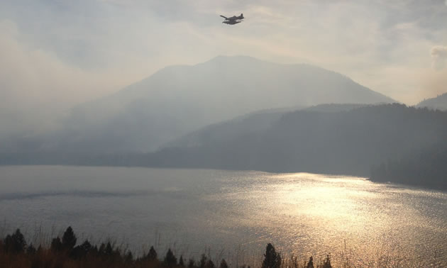 A water bomber is flying over Moyie Lake with the sun filtered by smoke.