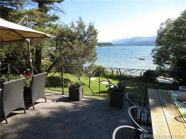 An image of the outdoor back deck with a large table for entertaining and a view of the lake.