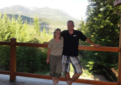 Man and woman on a deck in front of the mountains