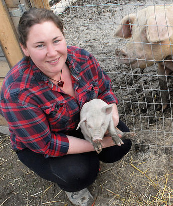 Jessica Piccinin with a piglette born on Root and Vine Acres in the Creston Valley.