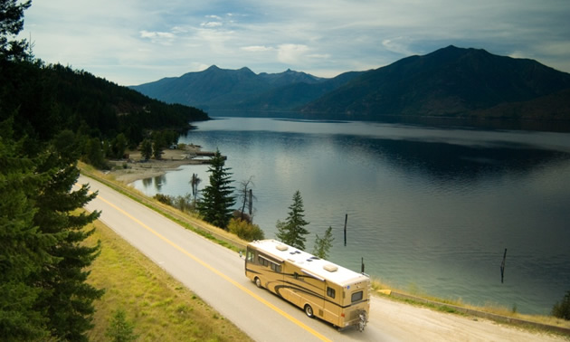 RV driving by beautiful lake