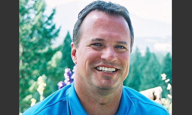 A man with a blue shirt smiles at the camera.