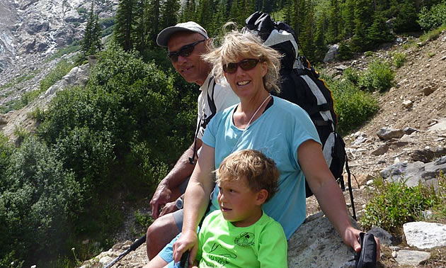 A man, woman, and child look at the camera while sitting on a mountain trail.