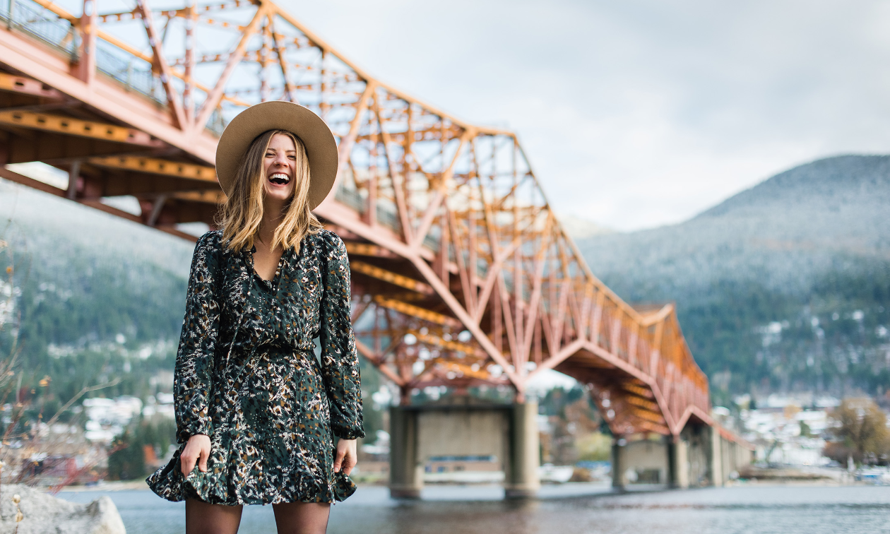 Amanda Mary laughs while wearing a dress in front of an orange bridge in Nelson, B.C.
