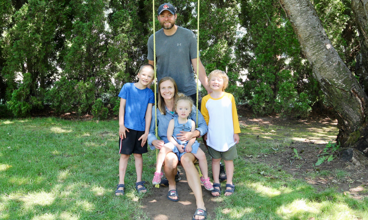 Trent and Emily Mason pose with their three children on a swing in the shade.