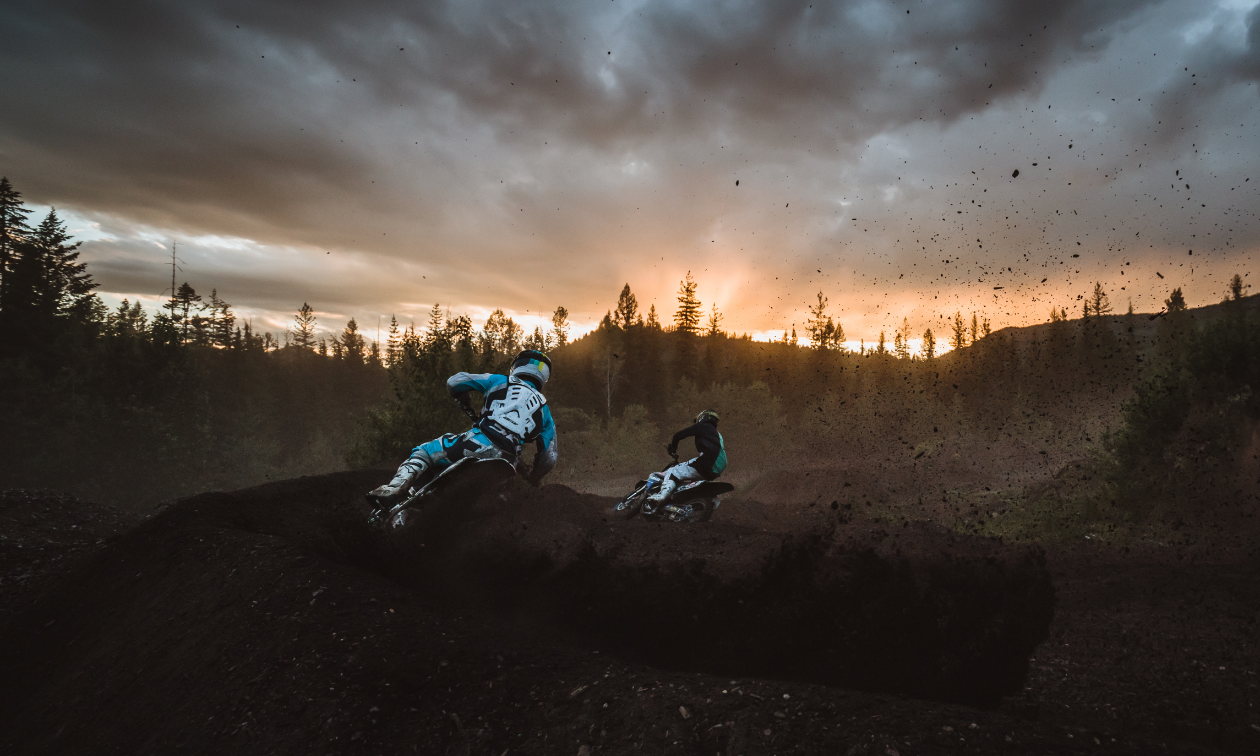 Two dirt bikers take a sharp turn at the West Kootenay Recreational Dirt Bike and ATV Society motocross track at dusk.