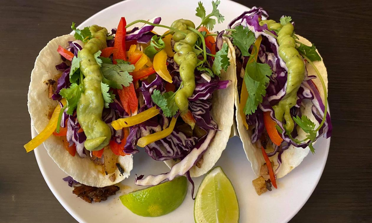 Jerk tacos on a plate on a table.