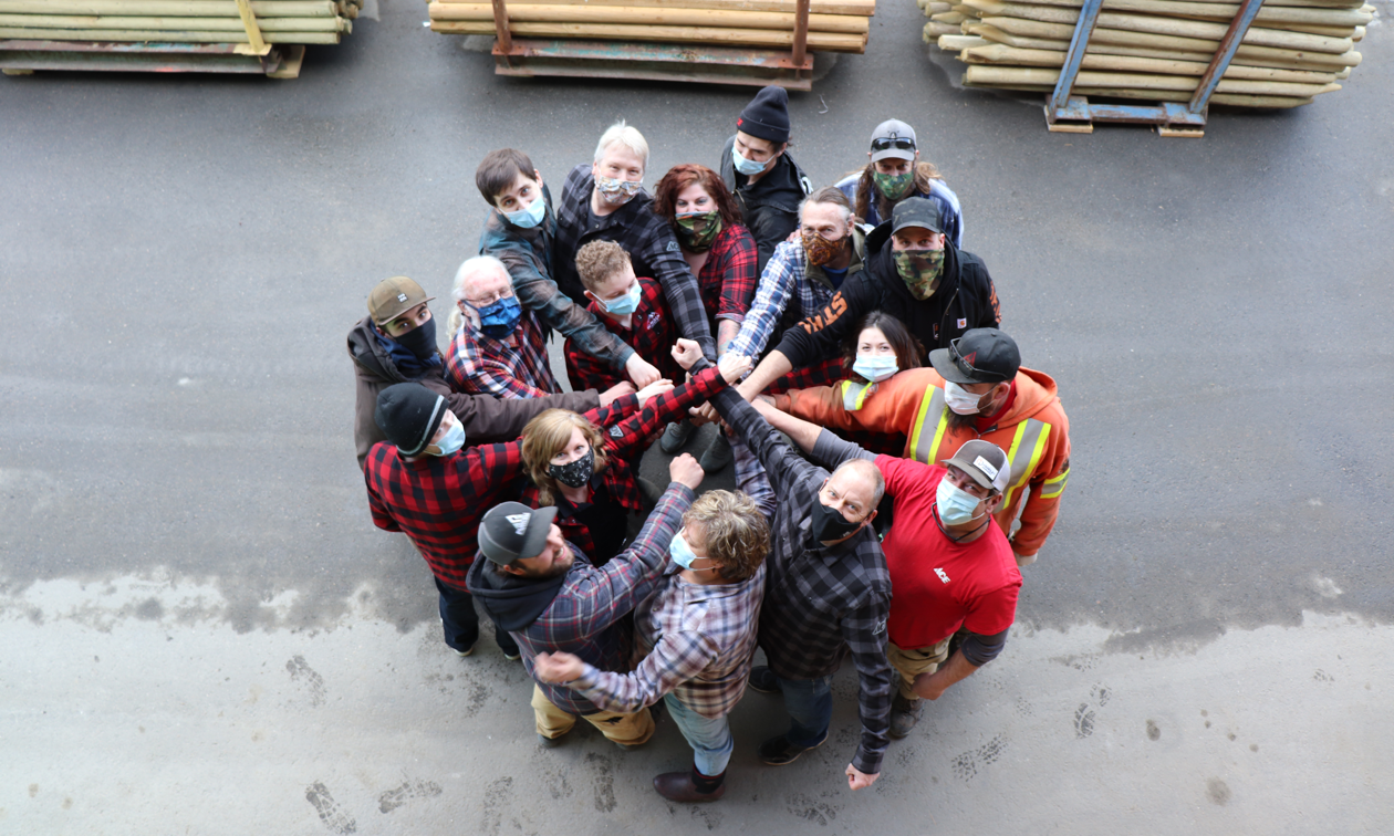 Jeff Davie (lower right with black mask), his wife, Monica Davie (very bottom, to the left of Jeff), and the team at Kaslo Building Supplies pose for a top-down photo where the group is in a circle and everyone is wearing a mask.