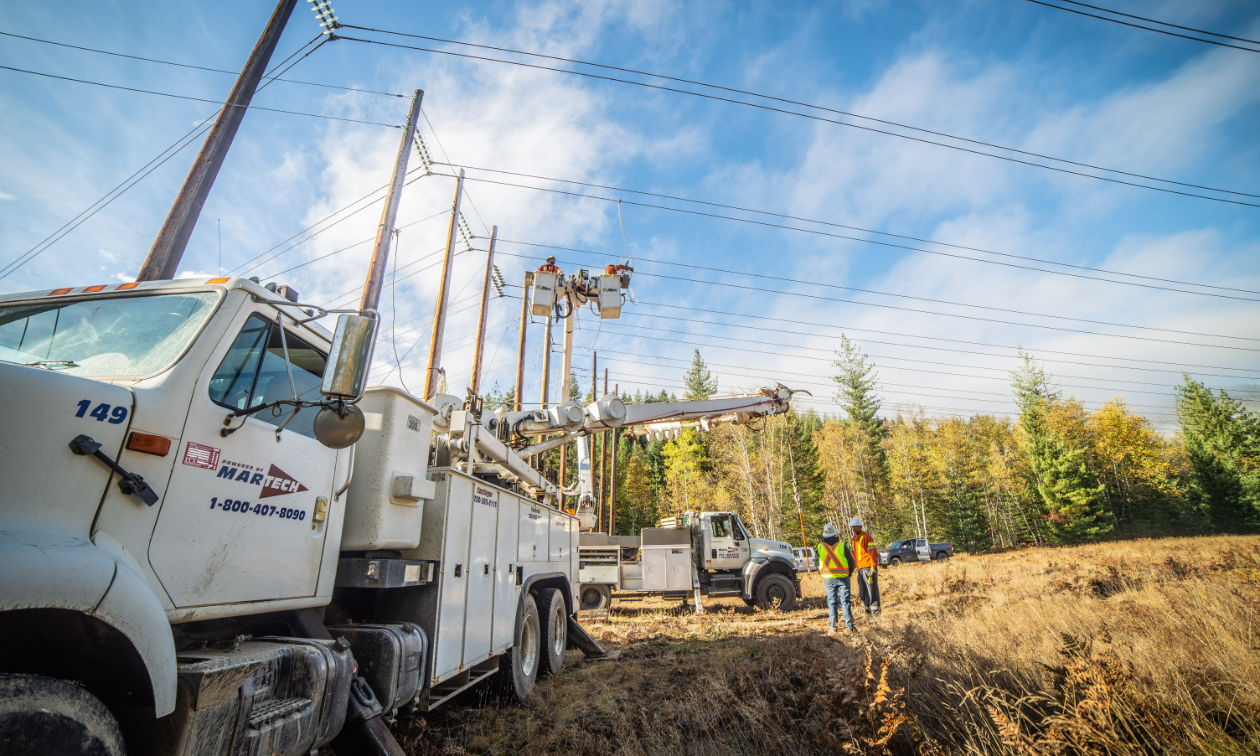 A Martech truck next to several large power poles.