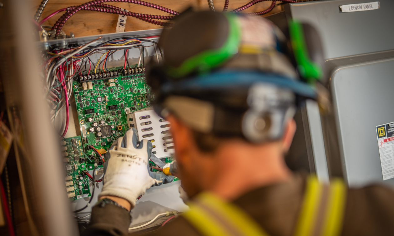 An electrician inspects a circuit board while wearing gloves and a hard hat.