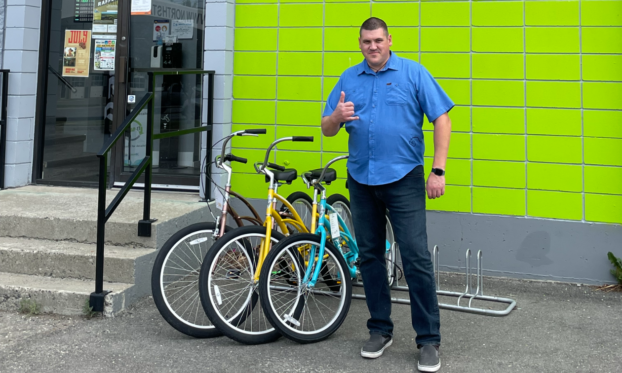 Jared Williams stands in front of Northstar Bicycle Co., a lime green building in Cranbrook, B.C.