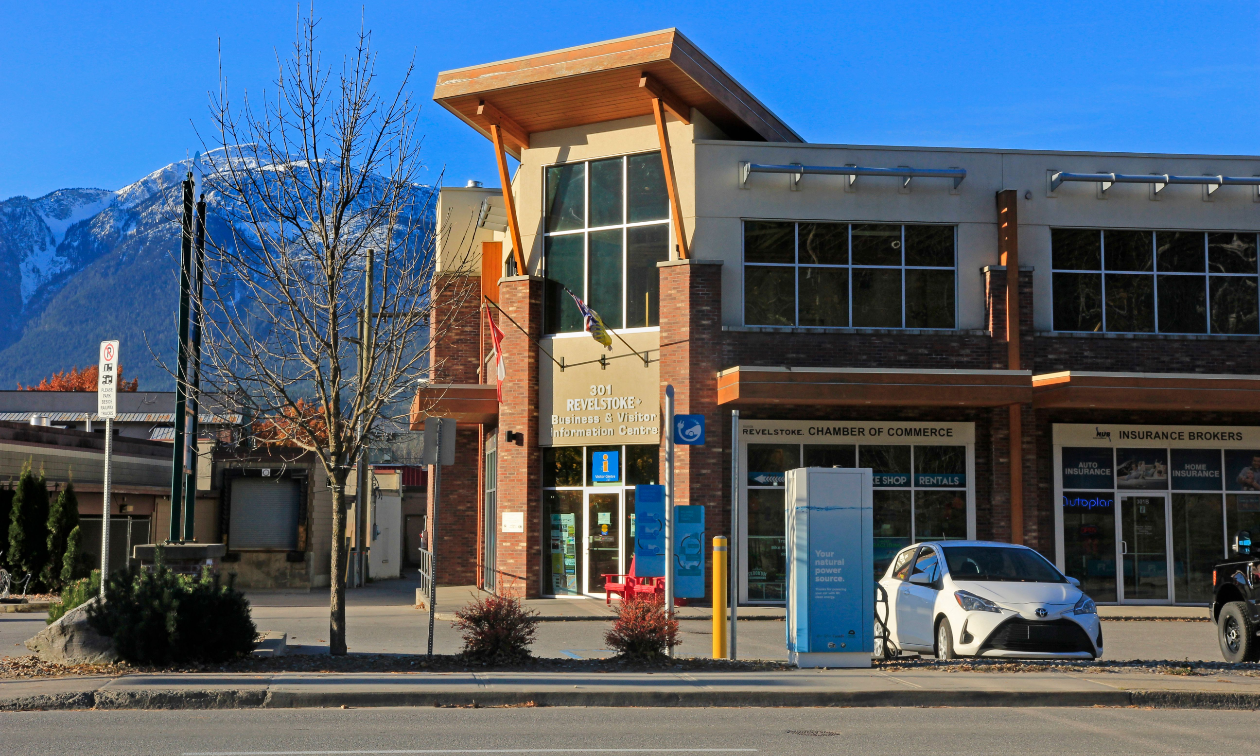 The Revelstoke Chamber of Commerce is a tan and brown building in downtown Revelstoke. Mountains are in the distance.