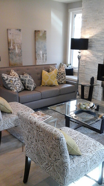 The living room at a staged home in inner city Calgary.  Grey couch with throw cushions as accents.