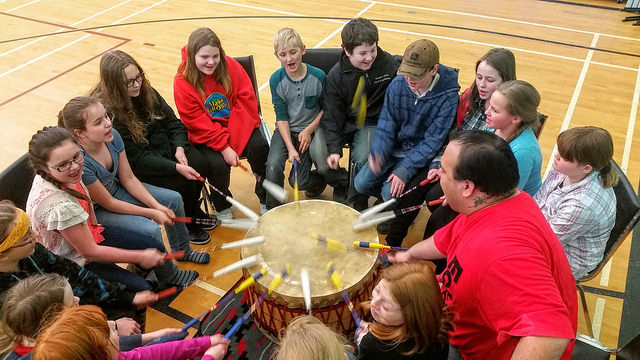 A group of children are sitting in a circle around a drum. All the children have a drumstick in hand and are participating in beating the drum.