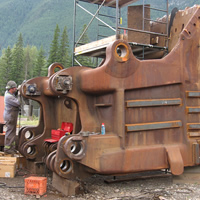 A welder working on a giant shovel head.