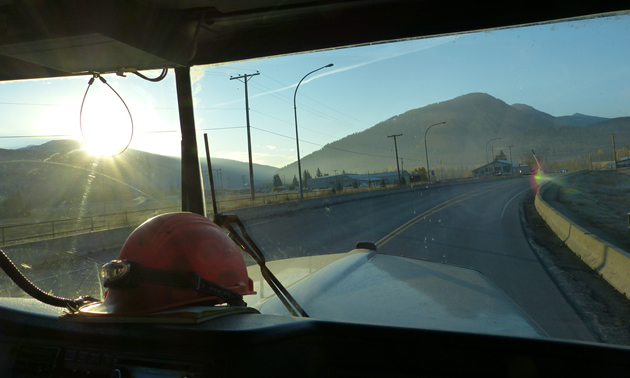 A view of the sun coming up over the mountains from the inside of a logging truck.