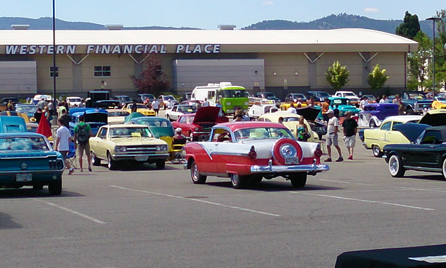 A red and white car surrounded by other classic cars in a parking lot.