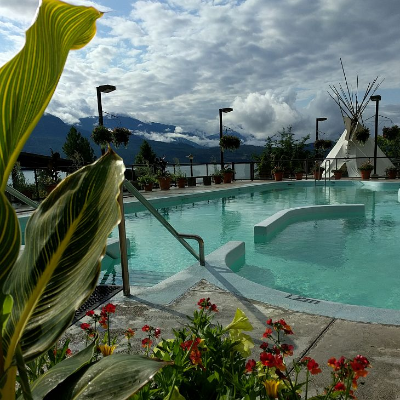 Ainsworth Hot Springs. A tranquil pool with a teepee in the background and mountains further away.