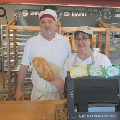 Rod and Tamara Duggan are standing behind the counter of Cobs Bread Bakery and Tamara is holding a loaf of bread.