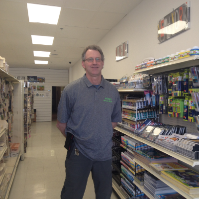 Fred Searle is standing in the crafts store near a row of paints and stretched canvases.