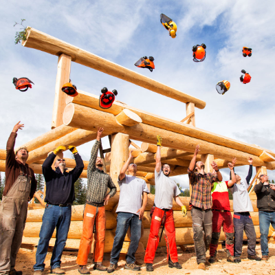 Carpenters throw their hard hats in the air in front of a log building.