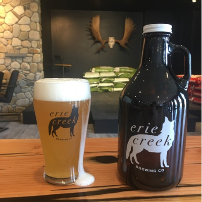A glass and growler full of beer on a table with Erie Creek Brewing Company's logo on the front.