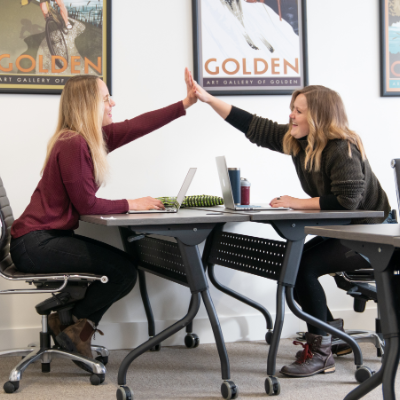 Two women high-five while sitting across from each other at desks.