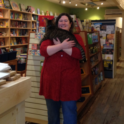 Erin Dalton holding cat in her bookstore.