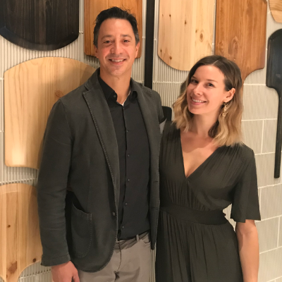 Ryan and Lea Martin, owners of Marzano, stand in front  of a wall with pizza paddles on the wall.