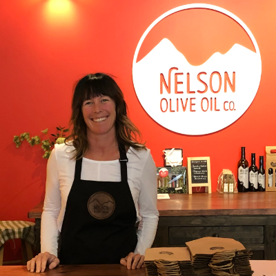 Michelle Rudell stands behind the counter in her store, Nelson Olive Oil.
