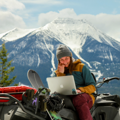 Brittney Dickson sits on her snowmobile while looking at her laptop in the mountains.
