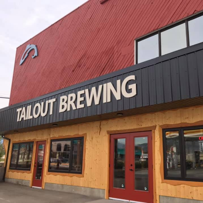 The front of Tailout Brewing is beige with maroon accents and a brown roof.