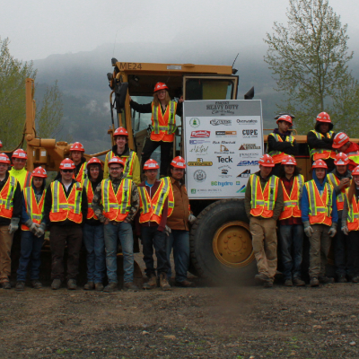 Students wearing orange and yellow vests pose in front of heavy machinery for Worksafe BC