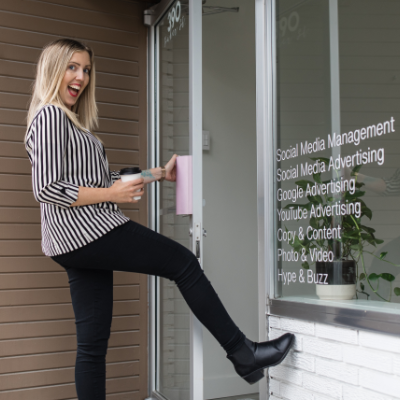 Zan Comerford smiles while kicking her leg up to open the door to her business, Liteworks Marketing.