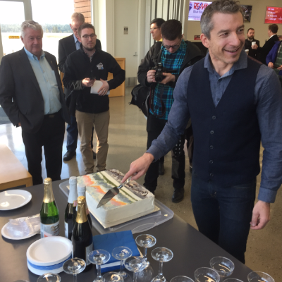 Tristen Chernove, CEO of Elevate Airports, cuts celebratory cake at announcement that WestJet and Pacific Coastal Airlines have partnered to bring jet service (Calgary to Cranbrook) to Canadian Rockies International Airport.