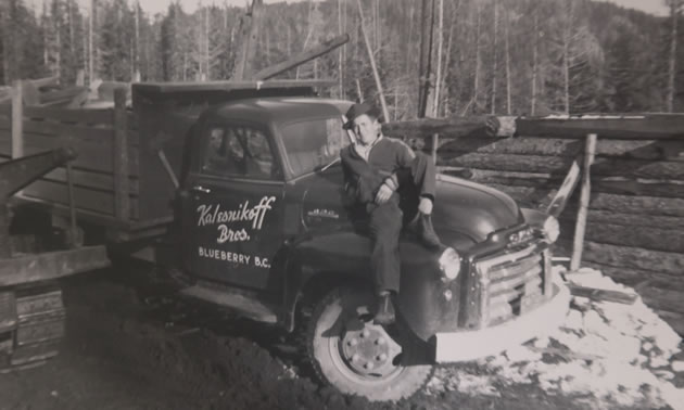 An old black and white photo of a man standing by an old truck.