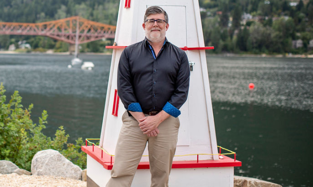 Colin White stands in front of an orange bridge in Nelson, B.C.