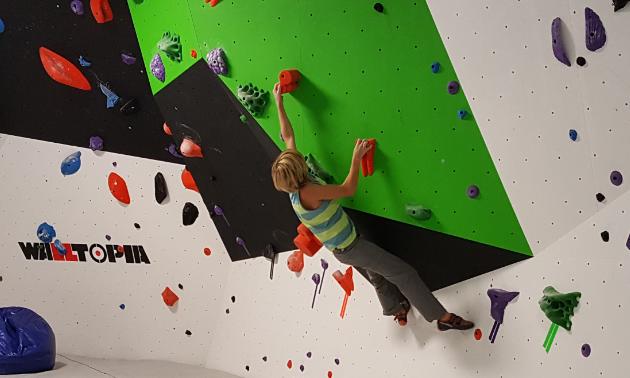 A child climbs a wall at Arq Mountain Centre.