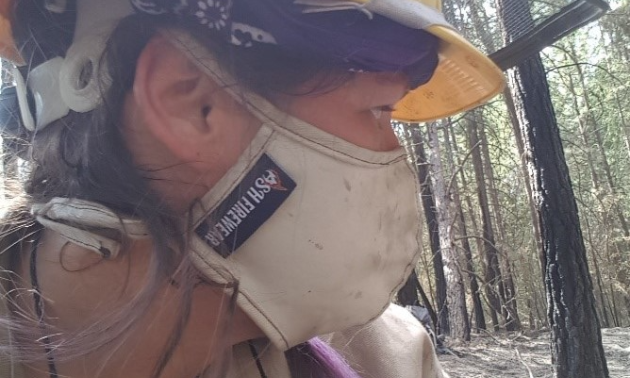 A female firefighter wears a yellow hard hat and a mask that says AshFireWear.