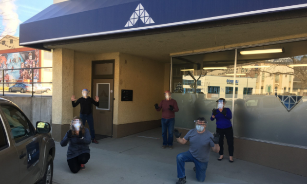 Five workers pose with face shields outside of Austin Innovation.