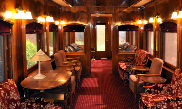 An old train car has wooden walls and a maroon carpet. It is furnished with beige and dark red chairs.
