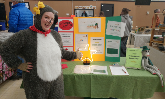 Lisa Aasebo-Kennedy is dressed up like a squirrel in front of an informational stand at a farmers market in Cranbrook.