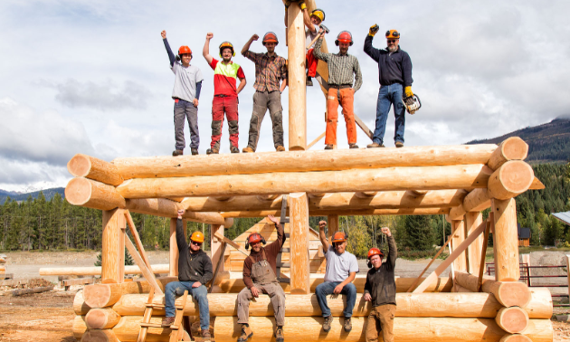 A group of carpenters hold up their fists on a log building.