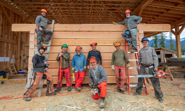 Carpenters line up inside a log building to pose for a photo.