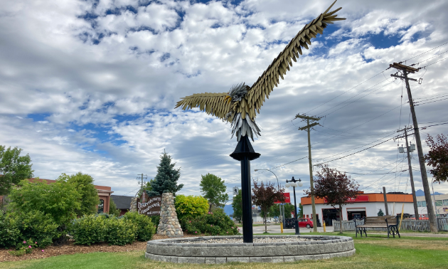 A large eagle made of steel framework resides next to a Welcome to Cranbrook sign.