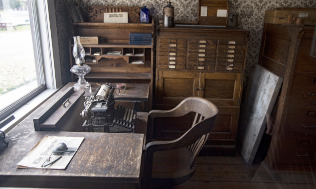 A typewriter sits on an old, worn brown desk next to old cabinets in an office.