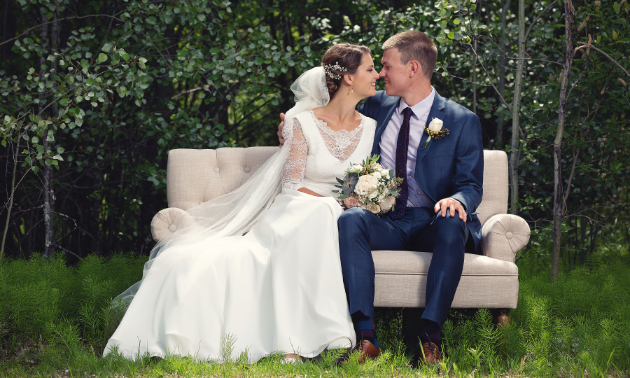 A married couple sits on a modern couch in the woods