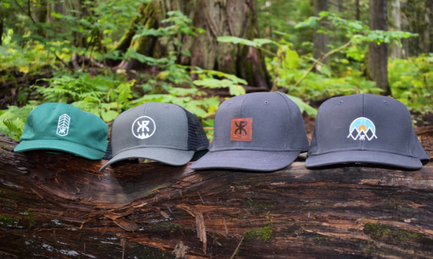 Four beige and green hats are lined up on a log in the woods.